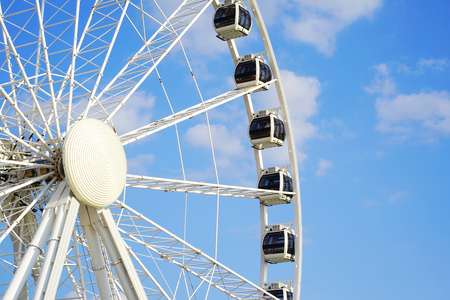 Part of white ferris wheel against blue cloudy sky background. Close-up of swirling big wheel against of blue cloudy sky