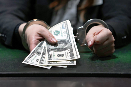Woman in office in handcuffs holding a bribe of 100 dollars banknote. Arrested terrorist. Financial crime, dirty money and corruption concept. Selective focus.