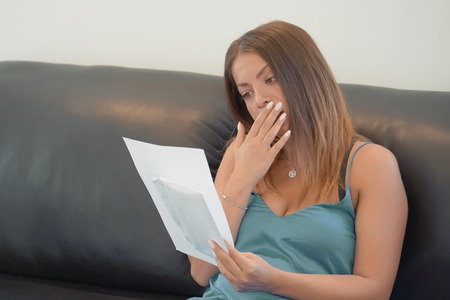 Woman reads negative news in a letter at home on the couch. An agitated girl without joy. Reklamní fotografie