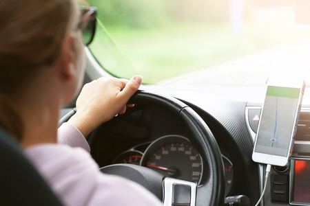 Hands of a woman with a steering wheel, Driving a car on a smartphone navigator. Photo of a young woman driving a car. Rear view and rear view of a young beautiful woman driving a car.