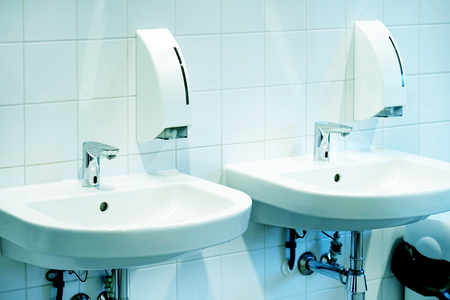 Bathroom interior sink with modern design. Interior of bathroom with washbasin and faucet. Close-up of bathroom. White bathroom. Public bathroom in the airport or restaurant, cafe.