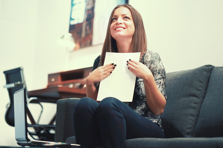 Woman enjoying good news in a letter. Happy brunette enjoying good news in written notice at home. Euphoric girl happy after reading good news in written letter, loan approvale. Toning