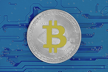 Bitcoin on dark blue circuit board. Bitcoin cryptocurrency on computer electronic circuit board. Cybercrime background
