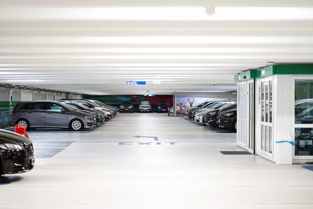 Parken von Autos ohne Menschen. Viele Autos im Parkhausinnenraum, Industriegebäude Tiefgarage mit Autos. Standard-Bild