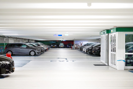 Parking cars without people. Many cars in parking garage interior, industrial building. Underground parking with cars.