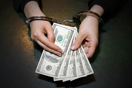 Woman in office in handcuffs holding a bribe of 100 dollars banknote. Arrested terrorist. Financial crime, dirty money and corruption concept. Selective focus. Toning