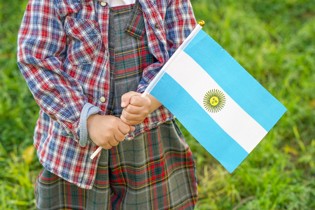 Hands of boy holding Argentina flag. Independence Day concept. Green grass background.