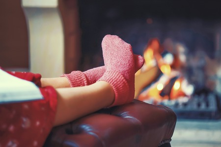 Woman in warm socks resting near fireplace at home with book. Woman feet with socks sitting near fireplace with a warmth background. Toning.