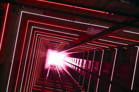 Elevator corridor in the building lit by red elumination. Futuristic elevator shaft is located in a high tower. Lift shaft in a residential building. Abstract, background. Bottom view.