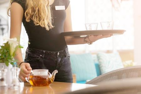 La serveuse porte du thé. Serveuse tenant un plateau avec une tasse de thé et une théière en verre pour le client du restaurant. Le concept de maintenance et de service. Banque d'images