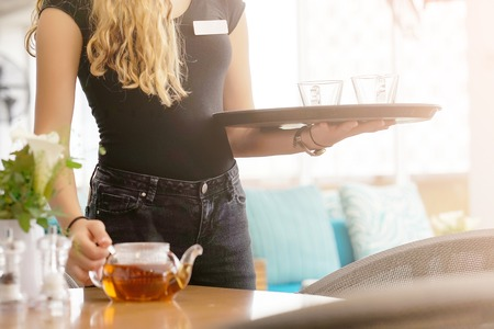 The waitress is carrying tea. Waitress holding tray with cup of tea and tea glass teapot for the client at the restaurant. The concept of maintenance and service. Banque d'images