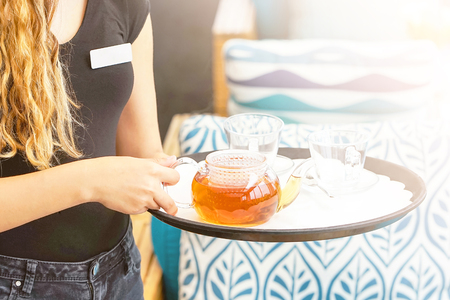 A waitress is carrying tea. Hospitable girl waitress holding tray with cup of tea and tea glass teapot for the client at the restaurant. The concept of maintenance and service.