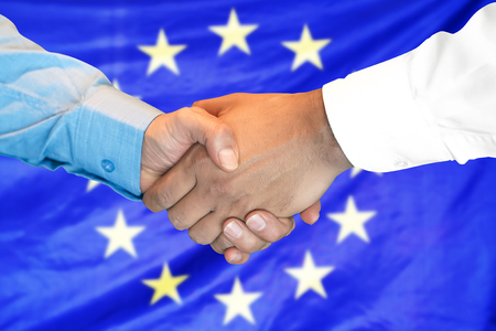 Business handshake on European Union flag background. Men shaking hands and European Union flag on background. Support concept Imagens