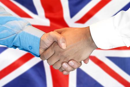 Business handshake on United Kingdom flag background. Men shaking hands and flag on background. Support concept Reklamní fotografie