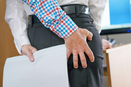 Hand Sexually Harassing Boss hugs his woman subordinate in office By Touching Her Ass. Sexual harassment at work. Man touching woman's butt Stock Photo