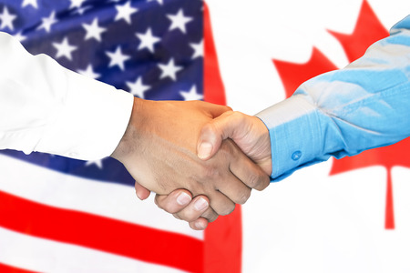 Business handshake on the background of two flags. Men handshake on the background of the Canada and United States of America flag. Support concept Reklamní fotografie