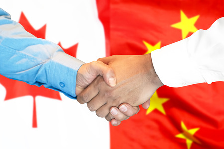 Business handshake on the background of two flags. Men handshake on the background of the Canada and China flag. Support concept
