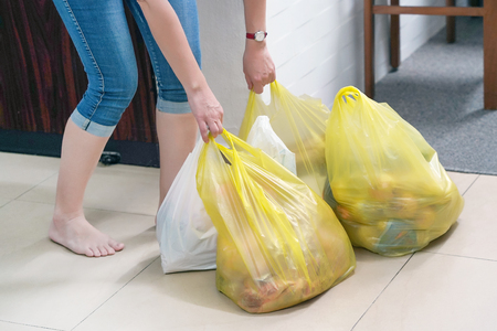 Woman with food plastic bags at home. Housewife with food packages after a supermarket in the hallway of her apartment. Stockfoto