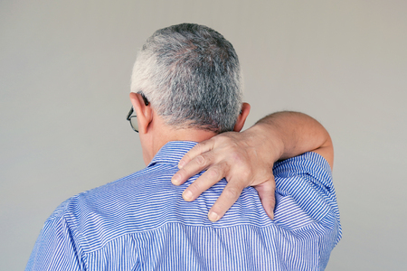 Elderly man suffering from neck pain isolated on a gray background. A man's sense of fatigue, exhausted, stressed. Old man massages her painful neck with her hands. The concept of body and health.