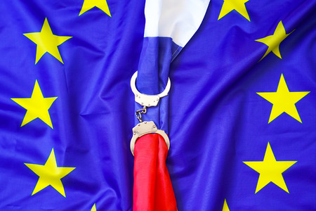 Flag of Russia in Handcuffs on the background of the flag of the European Union. European Union sanctions against Russia, chained handcuffs, political or economic conflict. The concept of sanctions. Zdjęcie Seryjne