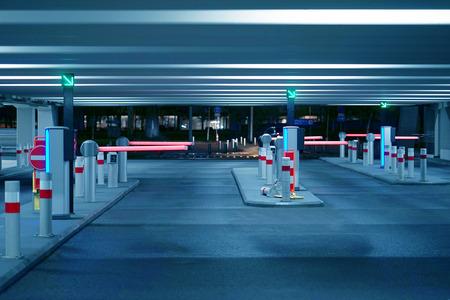 Schranke bei Ein- und Ausfahrt eines Autoparkhauses Schranke auf einem Parkplatz. Ausfahrt aus der Tiefgarage. Tiefgarage/Garage. Innenraum des Parkplatzes. Toning Standard-Bild