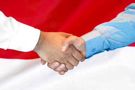 Business handshake on Monaco flag background. Men shaking hands and Monaco flag on background. Support concept