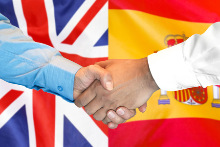 Business handshake on the background of two flags. Men handshake on the background of the Spain and United Kingdom flag. Support concept