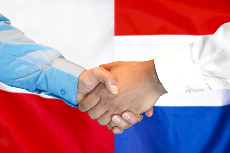 Business handshake on the background of two flags. Men handshake on the background of the Poland and Dutch flag. Support concept Imagens