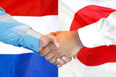 Business handshake on the background of two flags. Men handshake on the background of the Japan and Dutch flag. Support concept