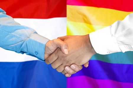 Business handshake on the background of two flags. Men handshake on the background of the LGBT gay and Dutch flag. Flag of tolerance. Support concept Imagens
