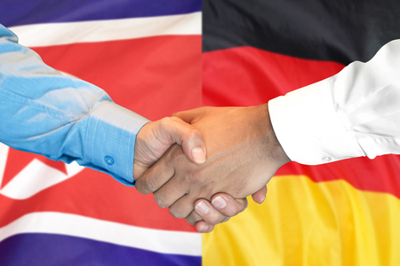 Business handshake on the background of two flags. Men handshake on the background of the North Korea and Germany flag. Support concept