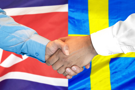 Business handshake on the background of two flags. Men handshake on the background of the North Korea and Sweden flag. Support concept