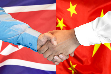 Business handshake on the background of two flags. Men handshake on the background of the North Korea and China flag. Support concept