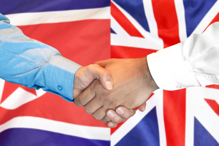Business handshake on the background of two flags. Men handshake on the background of the North Korea and United Kingdom flag. Support concept