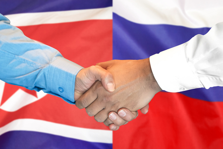 Business handshake on the background of two flags. Men handshake on the background of the North Korea and Russia flag. Support concept