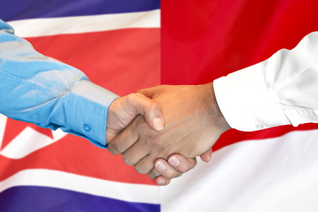 Business handshake on the background of two flags. Men handshake on the background of the North Korea and Monaco flag. Support concept Фото со стока