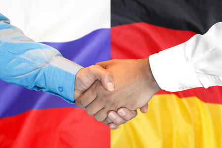Business handshake on the background of two flags. Men handshake on the background of the Germany and Russia flag. Support concept