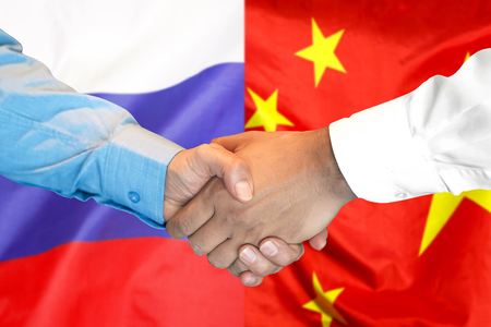 Business handshake on the background of two flags. Men handshake on the background of the China and Russia flag. Support concept