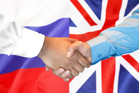 Business handshake on the background of two flags. Men handshake on the background of the United Kingdom and Russia flag. Support concept
