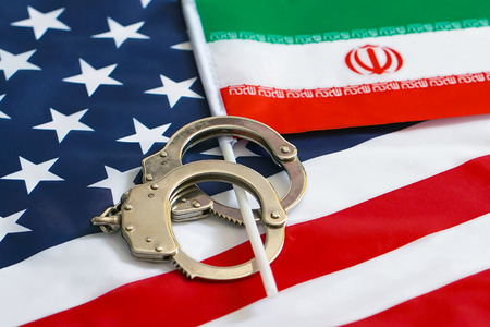 Iranian flag in handcuffs on the background of the American flag. US sanctions against Iran. Stock Photo - 124958881