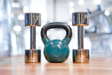 Blue kettlebell and chrome dumbbell on the floor in the gym