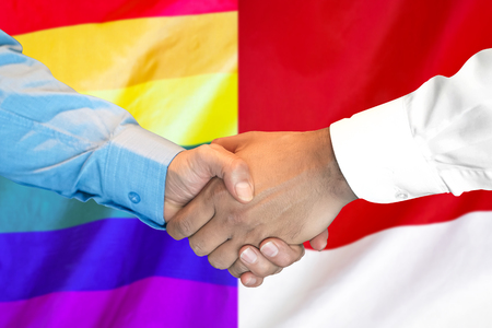 Business handshake on the background of two flags. Men handshake on the background of the Poland and Monaco flag. Support concept