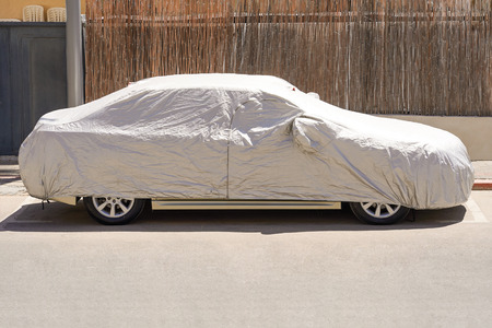 A car parked with protective cover silver. Car under a protective cover parked in the courtyard in sun weather, summer. Car with a protective, parking cover. The car is covered with a cover