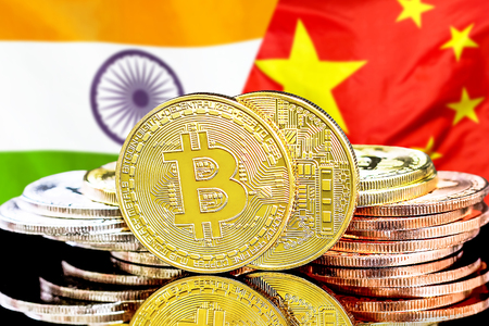 Concept for investors in cryptocurrency and Blockchain technology in the India and China. Bitcoins on the background of the flag India and China.