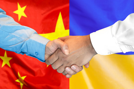 Business handshake on the background of two flags. Men handshake on the background of the China and Ukraine flag. Support concept