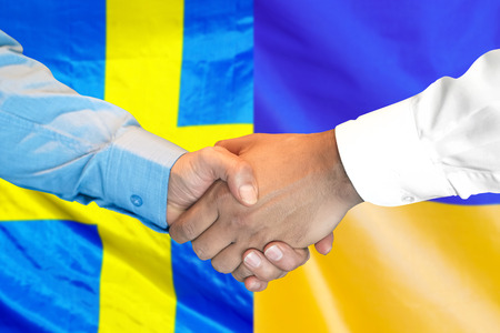 Business handshake on the background of two flags. Men handshake on the background of the Sweden and Ukraine flag. Support concept