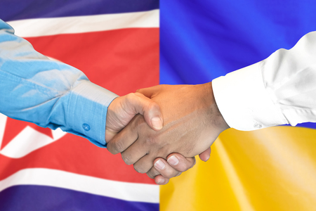 Business handshake on the background of two flags. Men handshake on the background of the North Korea and Ukraine flag. Support concept