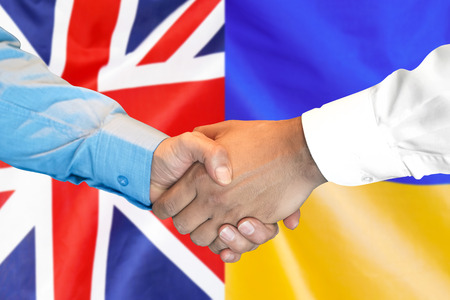 Business handshake on the background of two flags. Men handshake on the background of the United Kingdom and Ukraine flag. Support concept