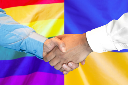 Business handshake on the background of two flags. Men handshake on the background of the LGBT gay and Ukraine flag. Flag of tolerance. Support concept