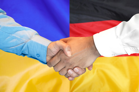 Business handshake on the background of two flags. Men handshake on the background of the Germany and Ukraine flag. Support concept